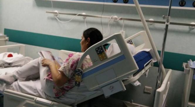 """Povestea din spatele fotografiei care a impresionat România! """"La spital, o tânără asistentă îi citeşte o poveste unei fetiţe de cinci ani de etnie romă. A venit cu o carte, a întrebat-o pe mamă dacă ştie să citească. Nu ştie!"""""""